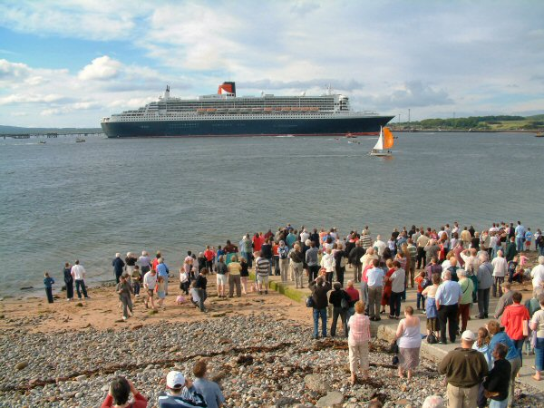 Crowds on the slip watch the QM2 leave the Firth
