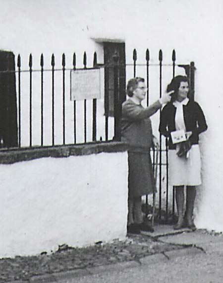 Woman talking outside Hugh Millers Cottage