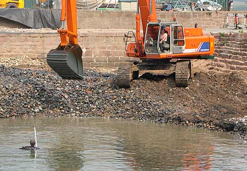 Harbour being dredged (with man in water)