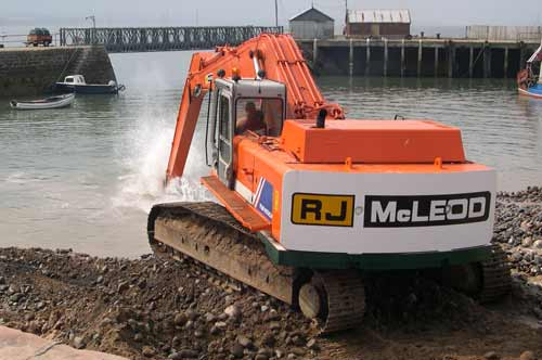 Digger dredging Harbour with pier in background